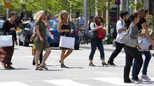 Pedestrians cross the Bloor Street, a high end shopping district, in Toronto. (Norm Betts/Bloomberg)