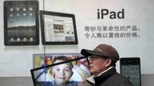 In this file photo taken on Jan. 26, 2011, a man stands near Apple's iPad advertisement in Shanghai, China. The official said Monday, Feb. 13, 2012, that investigators in Shijiazhuang, southwest of Beijing, started seizing iPads last week at the request of a company that filed a complaint with the government accusing Apple Inc. of violating its rights to the iPad name. (Eugene Hoshiko/Eugene Hoshiko/AP)