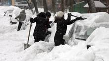 Motorists dig out their cars in Montreal on Dec. 15, 2013, as more than 20 cm of snow fell. (RYAN REMIOR/THE CANADIAN PRESS)