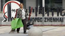 A cleaner walks past the logo for the Sinopec Zhenhai petrochemical factory, site of a controversial expansion proposal, where an expansion was proposed on the outskirts of Ningbo city in eastern China's Zhejiang province on Oct. 29, 2012. (Ng Han Guan/AP)