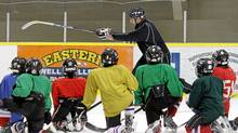 Coach Shane Doiron demonstrates a drill to his team, the Shediac Capitals in New Brunswicks' Atom Division, during practice in Shediac, New Brunswick on Monday, March 7, 2011. (Cole Burston for The Globe and Mail/Cole Burston for The Globe and Mail)