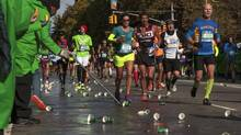 Runners in the New York City Marathon pass a refreshment station in the Harlem neighbourhood of New York on Sunday. Wilson Kipsang and Mary Keitany, both of Kenya, took first place in the men's and women's divisions of the race. (ANDREW WHITE/NYT)