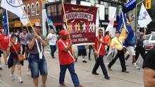 People take part in a Labour Day parade in Toronto, Monday, Sept.2, 2013. Union members have flooded the streets of Toronto in a spirited Labour Day celebration emboldened by the birth of the country's biggest union for private workers. (Will Campbell/THE CANADIAN PRESS)