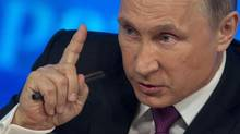 Russian President Vladimir Putin gestures during his annual news conference in Moscow on Dec. 18, 2014. (PAVEL GOLOVKIN/ASSOCIATED PRESS)