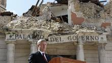 Canada's Prime Minister Stephen Harper speaks in front of buildings destroyed in the April earthquake in L'Aquila, Italy, on July 8, 2009. (CHRIS WATTIE)
