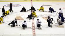Canadian junior players stretch at centre ice. (Ryan Remiorz/The Canadian Press)