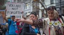 A woman scatters rose petals on Hastings Street during the 27th annual Women's Memorial March in the Downtown Eastside of Vancouver, B.C., on Tuesday February 14, 2017. (Darryl Dyck For The Globe and Mail)