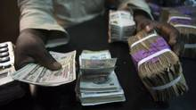 A trader changes dollars with naira at a currency exchange store in Lagos, Nigeria. An almost 40 per cent devaluation of the naira against the U.S. dollar in June has failed to rectify severe shortages of foreign exchange. (Joe Penney/Reuters)