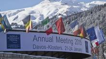 Flags hang on the roof of the Congress Hall where the World Economic Forum will take place in Davos, Switzerland. (MICHEL EULER/AP)