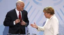 German Chancellor Angela Merkel, right, and Greek Prime Minister George Papandreou talk after speaking to reporters at the Chancellery in Berlin on Tuesday. (TOBIAS SCHWARZ/REUTERS)
