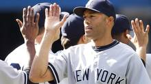 New York Yankees pitcher Mariano Rivera is congratulated by teammates after tying the major league all time saves record, in their MLB American League baseball game against the Toronto Blue Jays in Toronto September 17, 2011. Rivera tied the record of 601 career saves held by pitcher Trevor Hoffman. REUTERS/Fred Thornhill (FRED THORNHILL)
