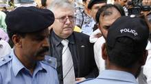 Police clear the way for Ukrainian Ambassador to Pakistan Volodymyr Lakomor (C) as he arrives to see the bodies of Ukrainian tourists, killed by unidentified gunmen near the Nanga Parbat peak, at a hospital morgue in Islamabad June 23, 2013. (STRINGER/PAKISTAN/REUTERS)