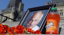 On the steps of Parliament Hill in Ottawa a photograph of Jack Layton is surrounded with flowers, a bottle of Orange Crush and other messages to commemorate the first anniversary of Layton's death, on Wednesday, August 22, 2012. (FRED CHARTRAND/THE CANADIAN PRESS)