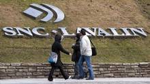 Pedestrians walk past the offices of SNC-Lavalin. (RYAN REMIORZ/THE CANADIAN PRESS)