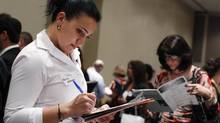 A woman fills out an application form from a jewelry and gem company during the Gemological Institute Of America (GIA)'s Jewelry Career Fair in New York July 30, 2012. (SHANNON STAPLETON/REUTERS)