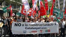 Catalunya Caixa workers and their families take part in a protest against the bank's restructuring in front of the bank's headquarters building in Barcelona. The banner reads: 'No to the restructuring of Catalunya Caixa.' (ALBERT GEA/REUTERS)