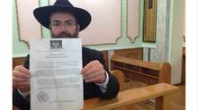 Chief rabbi of Donetsk holding leaflet calling on city's Jews to register. He calls it a 'provocation.' (Mark MacKinnon/Globe and Mail)