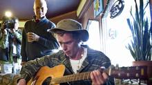 NDP Leader Jack Layton listens to Luc Lafleur play the guitar in a Courtenay, B.C., coffee shop during an April 7, 2011, campaign stop. (Paul Chiasson/THE CANADIAN PRESS)