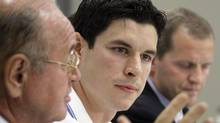 Pittsburgh Penguins' Sidney Crosby, center, and Dr. Michael Collins, right, listen as Dr. Ted Carrick, left, describes Crosby's progress in his recovery from a concussion he suffered in January 2011 during an NHL hockey news conference in Pittsburgh on Sept. 7, 2011. (Gene J. Puskar/The Canadian Press)