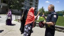 Police officer, Sgt. Chris Laush, gets a thumbs up from an elderly Somail woman in the area between 320, 330 and 340 Dixon Road in Toronto. (Peter Power/The Globe and Mail)