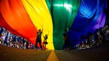 People carry an oversized rainbow flag down Robson Street during the Vancouver Pride Parade in Vancouver, B.C., on Sunday August 3, 2014. (DARRYL DYCK/THE CANADIAN PRESS)