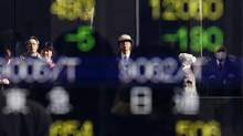 Pedestrians are reflected in an electronic board showing stock prices outside a brokerage in Tokyo on Dec. 12, 2013. (YUYA SHINO/REUTERS)