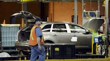 An employee walks as a vehicle on the production line at Ford Motor Co. of Canada's Oakville Assembly in this file photo. (Aaron Harris/Bloomberg)