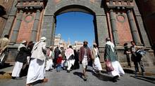 Yemeni people walk in front of the main entrance of Old Sanaa city on Jan. 7, 2010. (AHMED JADALLAH/AHMED JADALLAH/REUTERS)