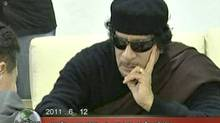 Libyan leader Moammar Gadhafi plays chess with Kirsan Ilyumzhinov, the president of the international chess federation, in Tripoli on June 12, 2011 in this still image taken from video broadcast on Libyan state television. (REUTERS TV/REUTERS)
