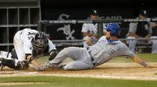 Chicago White Sox catcher Tyler Flowers, left, tags out Kansas City Royals' Danny Valencia at home on a throw from Alejandro De Aza, after Valencia tried to score from first on a double by Alcides Escobar, during the fourth inning of a baseball game Monday, July 21, 2014, in Chicago. (Charles Rex Arbogast/AP)