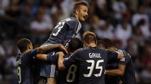 David Beckham of the L.A Galaxy celebrates teammate Jose Villarreal's goal against the Vancouver Whitecaps with teammates during the second half of their MLS game in Vancouver, British Columbia July 18, 2012. (BEN NELMS/REUTERS)