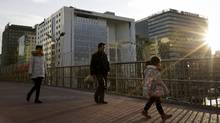 A Chinese family walks on a pedestrian overhead bridge near the office building of the China National Chemical Corp., also known as ChemChina, in Beijing, on Feb. 4, 2016. ChemChina's $43-billion (U.S.) bid for Switerzland's Syngenta AG makes a towering statement about China's ambitions as a global acquirer. (Andy Wong/AP)