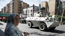 A Uighur woman stands near a small mosque where a paramilitary police Armored Personnel Carrier is parked in Urumqi, western China's Xinjiang province, Thursday, July 9, 2009. (Eugene Hoshiko/The Associated Press/Eugene Hoshiko/The Associated Press)