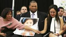 Jimmy Greene holds a photo of his daughter, Ana Marquez-Greene, 6, one of the victims of the shooting at Sandy Hook Elementary School, as his wife, Nelba Marquez-Greene, right, is comforted by her mother during a news conference to call for a national dialogue on gun violence. Relatives of 11 of the children and adults killed at the school have formed a group to join the national debate on gun violence. (OZIER MUHAMMAD/NYT)
