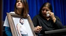 Amritpal Saran's mother Jitinder Saran, right, wipes away tears as his sister Simrit Saran holds a photo of her late brother during an Integrated Homicide Investigation Team news conference announcing charges in his death, at RCMP headquarters in Surrey, B.C., on Monday January 6, 2014. Two Surrey residents have been charged in relation to the deaths of Amritpal Saran, Karen Nabors and Jill Lyons. (DARRYL DYCK/THE GLOBE AND MAIL)