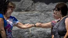 Two women smile and clasp arms following a moment of silence at noon in Lac-MÈgantic, PQ on July 13, 2013. (Peter Power/The Globe and Mail)