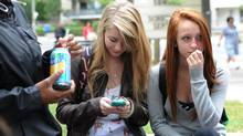 Sixteen-year-old Danica Ruttle, left, and fifteen-year-old Clarissa Stinson use their cell phones at Parkdale Collegiate Institute in Toronto, Ont. on Sept. 6, 2011. (KEVIN VAN PAASSEN/THE GLOBE AND MAIL)