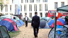 "A businessman passes tents belonging to the ""Occupy the London Stock Exchange"" protestors at their camp at Finsbury Square near London's financial district, Thursday, Nov. 17, 2011. (Chris Ratcliffe/Bloomberg)"