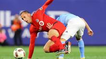 David Villa of New York City FC and Benoit Cheyrou of Toronto FC get tangled up vying for the ball at Yankee Stadium on March 13, 2016. (Mike Stobe/Getty Images)