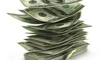 flying dollar bills in stack, the concept of success (urfinguss/Getty Images/iStockphoto)