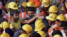 India's National Disaster Response Force personnel stand around a man, left, they rescued from beneath the debris of a building that collapsed on the outskirts of Chennai, India, on July 1, 2014. (ASSOCIATED PRESS)