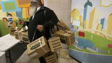 An ultra-Orthodox Jewish man carries gas masks and protection kits at a distribution point at a shopping mall in Pisgat Zeev, an urban settlement, on Jan. 30, 2013. A spokesperson for the Israeli postal service, responsible for the distribution of the protective kits, said on Wednesday that demand for the kits at distribution centers had doubled since the beginning of the week. (RONEN ZVULUN/REUTERS)