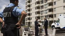 June 13, 2013: Police officers speak to a resident in front of a building that was raided early in the morning located at 320 Dixon Rd. (Philip Cheung For The Globe and Mail)
