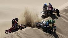 Vicente De Benedictis of Brazil (R) crashes on a dune in front of Pablo Copetti of Argentina (top R) and Christophe Geoffroy of France (L) during the seventh stage of the third South American edition of the Dakar Rally 2011 from Arica to Antofagasta January 9, 2011. (Eric Gaillard/Reuters)