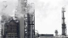 Smoke rises from stacks as processing slowly resumes at the Imperial Oil refinery in Nanticoke in 2007. The IMF is calling on Canada to impose raise carbon taxes, but reduce taxation on people. (J.P. MOCZULSKI/REUTERS)
