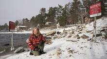 Peggy Peterson sits near the Bala Falls where a hydroelectric power plant is proposed on a section of Crown-land, in Muskoka Lakes, Ontario, on December 30, 2014. Red signs warn the public that use of the property is prohibited under section 28 of the Public Lands Act. Peterson, who is opposed to the project, has camped by the falls since September in protest. (Matthew Sherwood For The Globe and Mail)