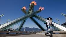 Vancouver Canucks' mascot Fin runs past the Olympic Cauldron after it was re-lit in honour of the Canucks NHL Stanley Cup Final hockey playoff run in Vancouver, B.C., on Monday June 6 2011. (The Canadian Press)