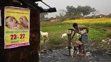 In this photo taken Jan. 23, 2011, a man bathes a child with water from a pump beside a polio awareness campaign poster on the wall of a small shop in the village of Kosi, about 180 kilometres from Patna, India. (Altaf Qadri/AP/Altaf Qadri/AP)