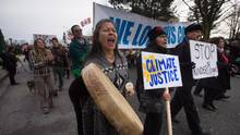 Patricia Kelly, left, of the Sto:lo First Nation, marches with Grand Chief Stewart Phillip, right, president of the Union of B.C. Indian Chiefs, to a protest outside National Energy Board hearings on the proposed Trans Mountain pipeline expansion in Burnaby, B.C., on Jan. 19, 2016. (DARRYL DYCK/THE CANADIAN PRESS)