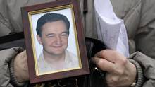 A portrait of lawyer Sergei Magnitsky who died in jail, is held by his mother Nataliya Magnitskaya, as she speaks during an interview with the AP in Moscow. (Alexander Zemlianichenko/AP)